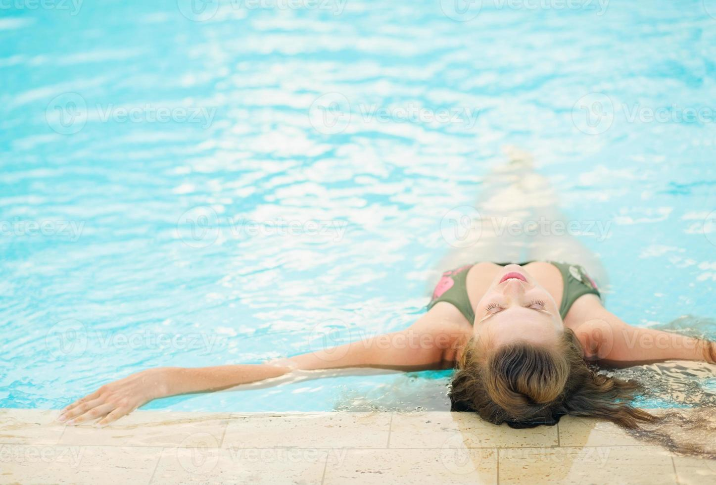 young woman enjoying pool . rear view photo