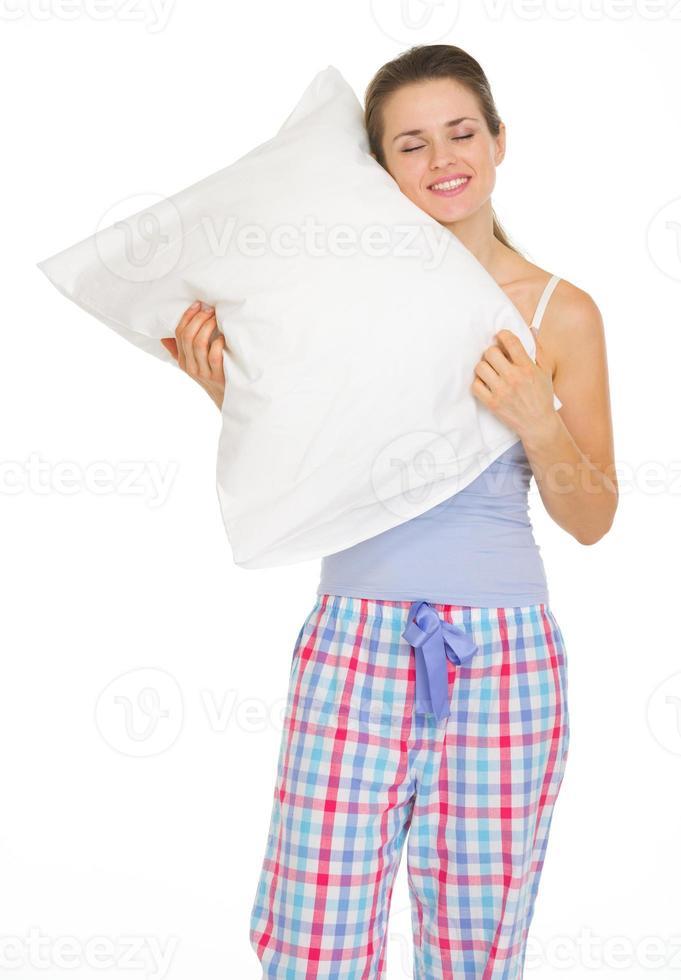 young woman in pajamas enjoying cosy pillow photo