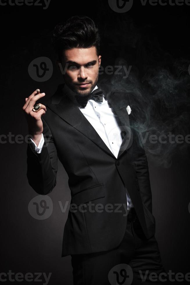 Handsome young business man enjoying a cigarette photo