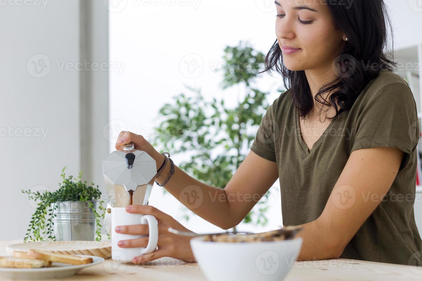 Hermosa joven disfrutando del desayuno en casa. foto