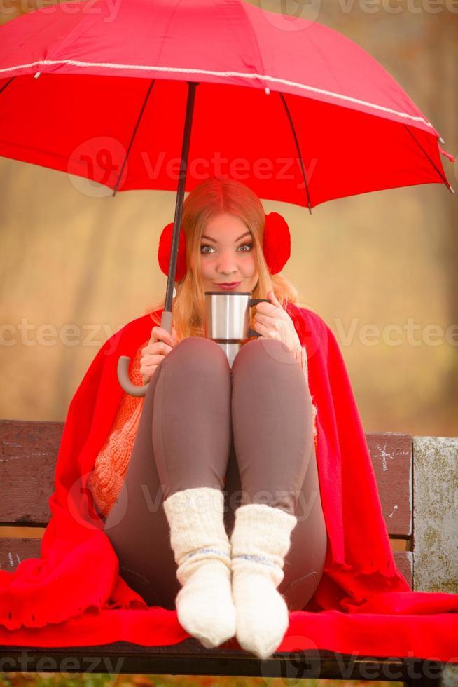 Girl in autumn park enjoying hot drink photo