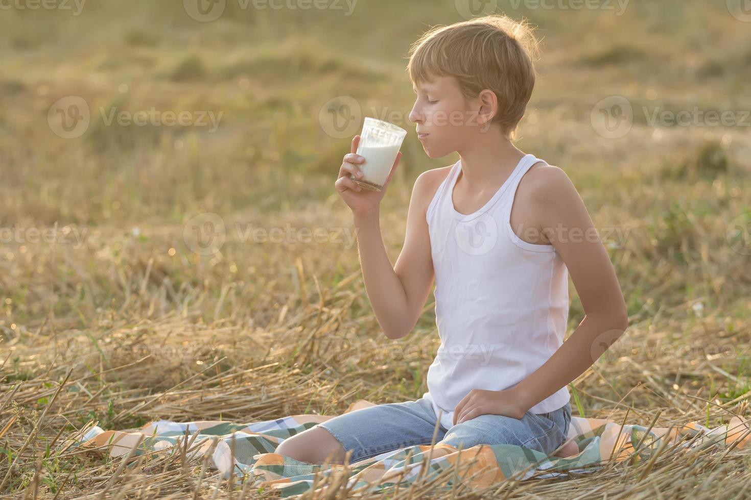 Teenage boy with closed eyes enjoys milk photo