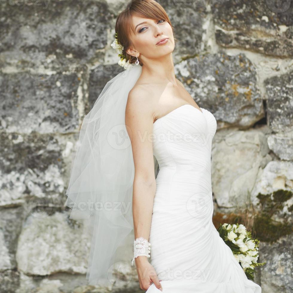 Gorgeous young bride enjoying wedding day. Summertime newlywed. photo