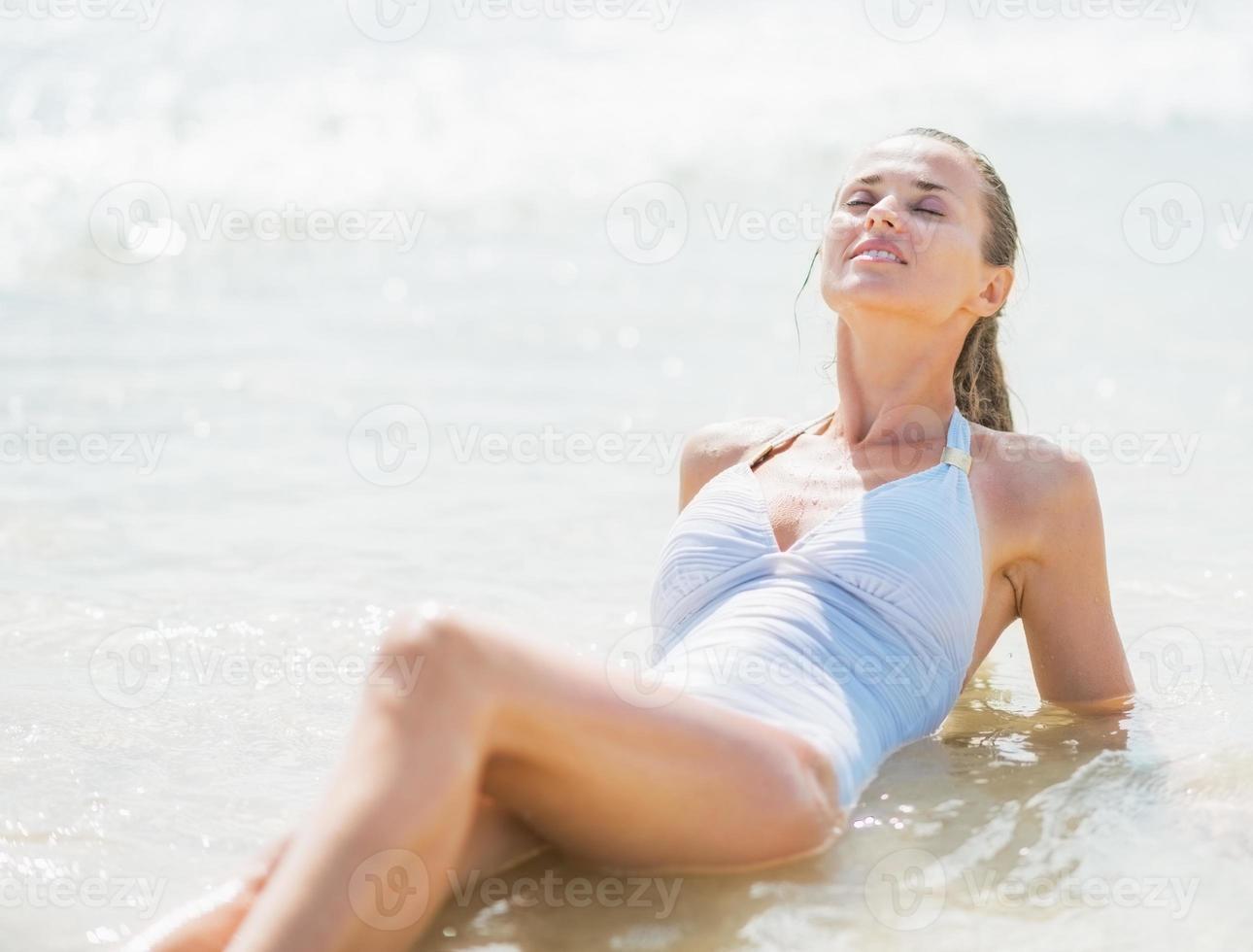 feliz joven disfrutando de la colocación en agua de mar foto
