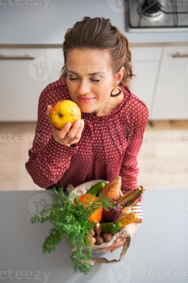 femme au foyer appréciant la fraîcheur des achats sur le marché local photo