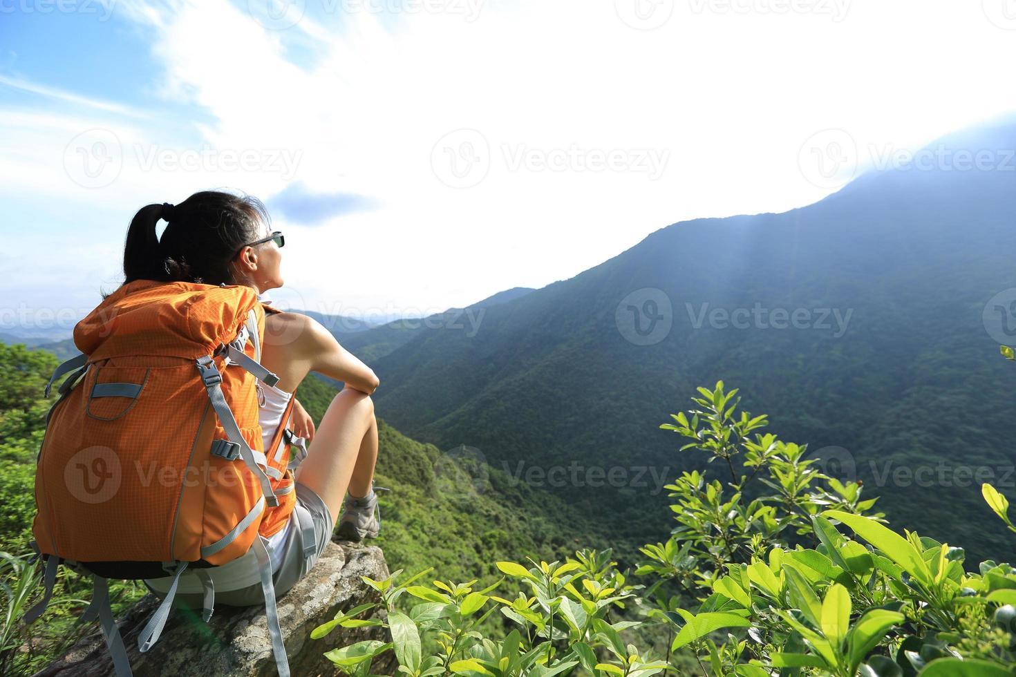 vrouw backpacker geniet van het uitzicht op de bergtop klif foto