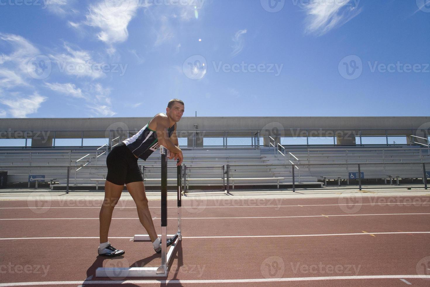 Male athlete resting arms on hurdle, side view (lens flare) photo