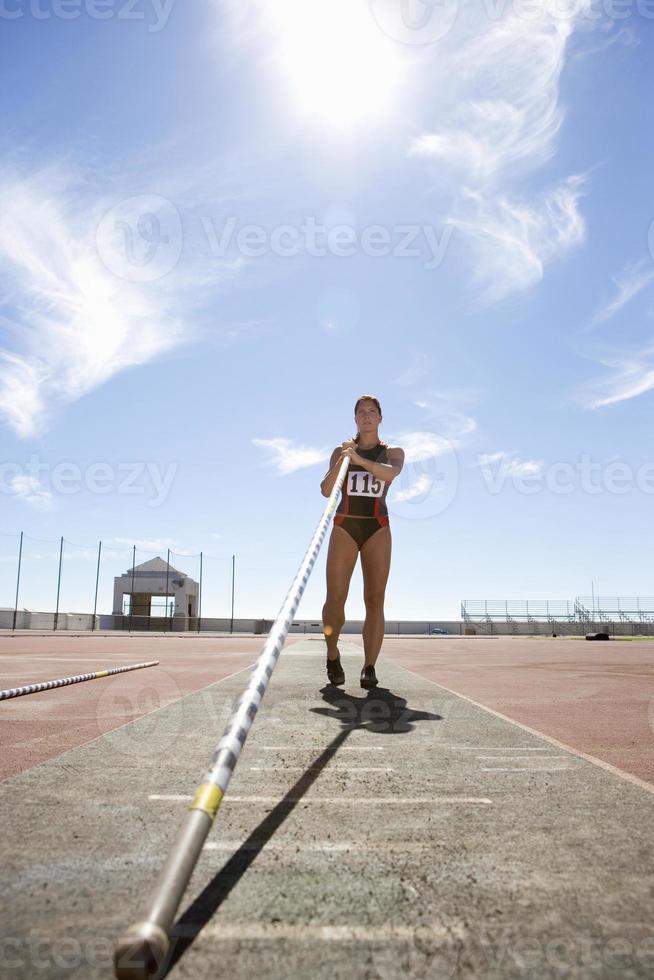 vrouwelijke polsstokspringen atleet met pole, lage hoek bekijken foto