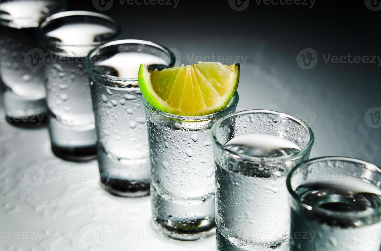 tequila y lima en mesa de vidrio foto