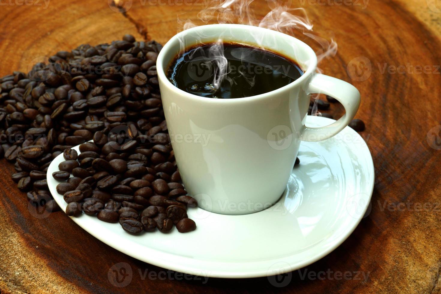 Taza de café y frijoles sobre un fondo de madera. foto