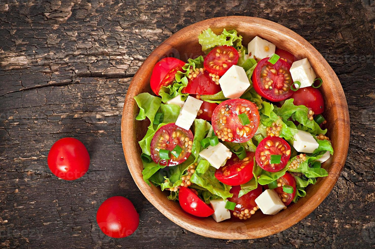 Tomato salad with lettuce, cheese and mustard and garlic dressing photo