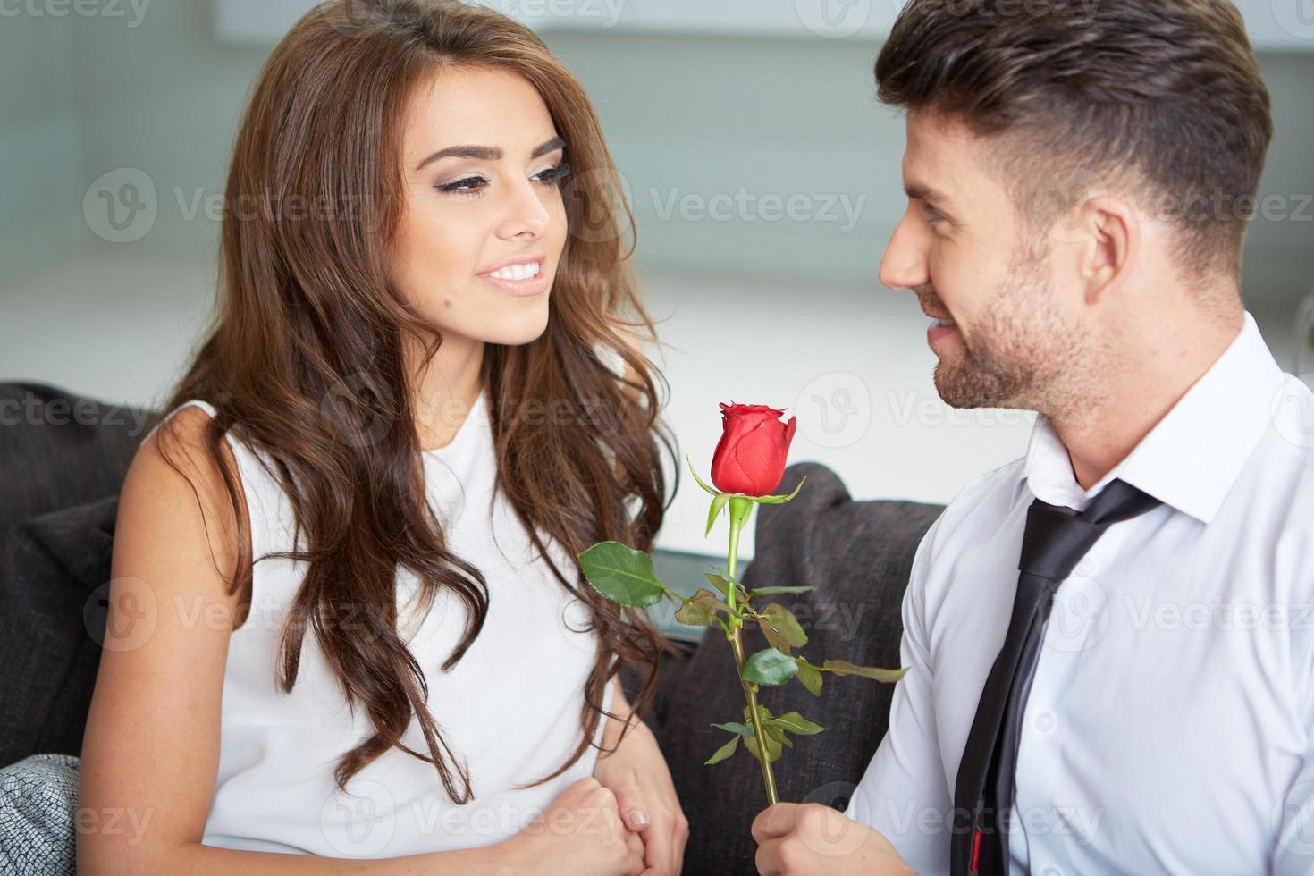 Portrait of two young people holding a rose photo