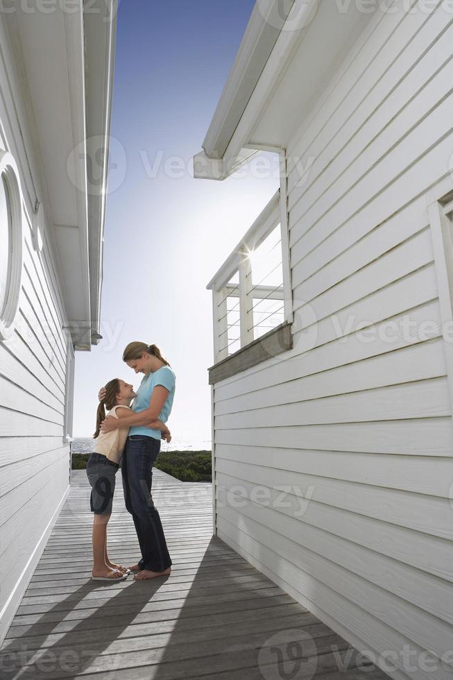 donna che abbraccia la figlia sul ponte foto