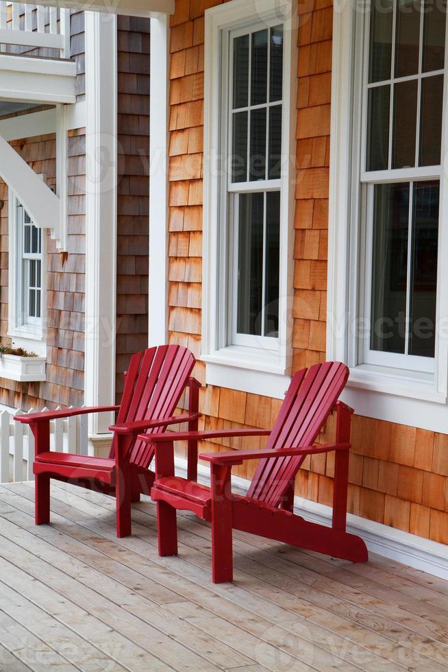 Two red Adirondack chairs photo