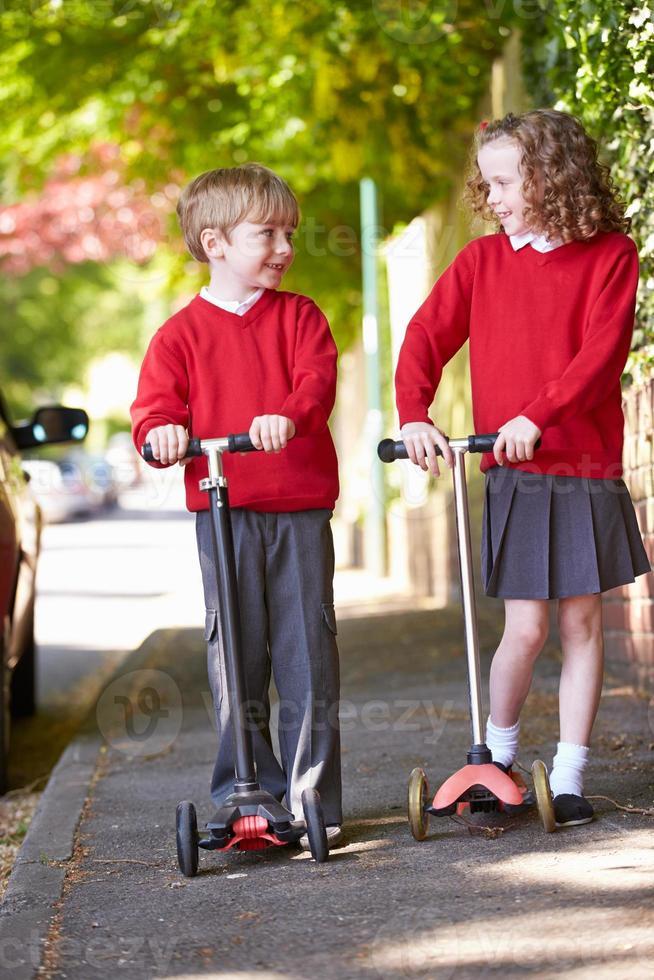 menino e menina andando de scooter a caminho da escola foto