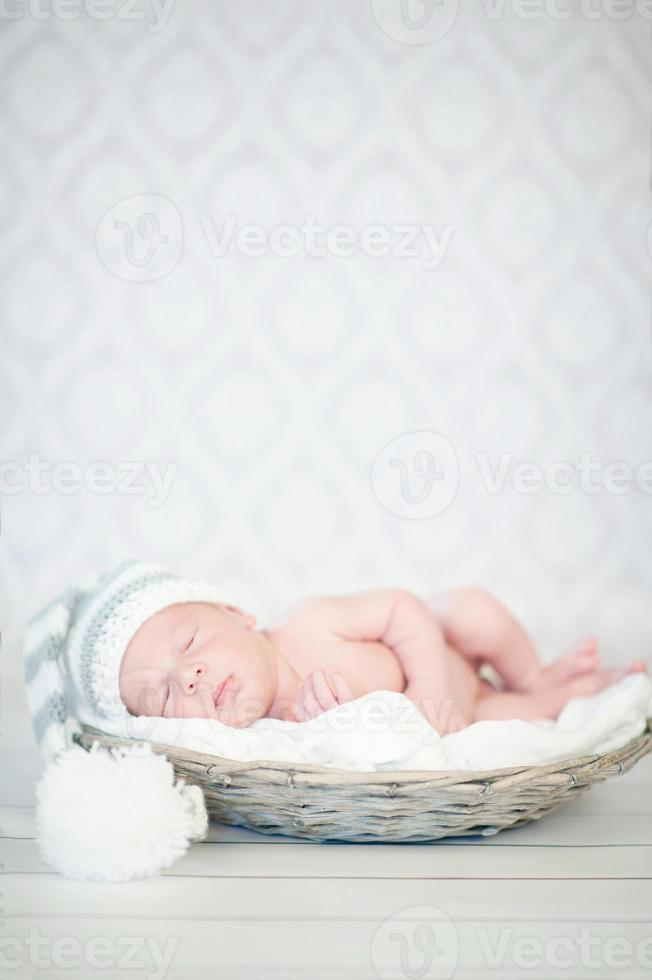 Foto de un bebé recién nacido acurrucado durmiendo en la canasta