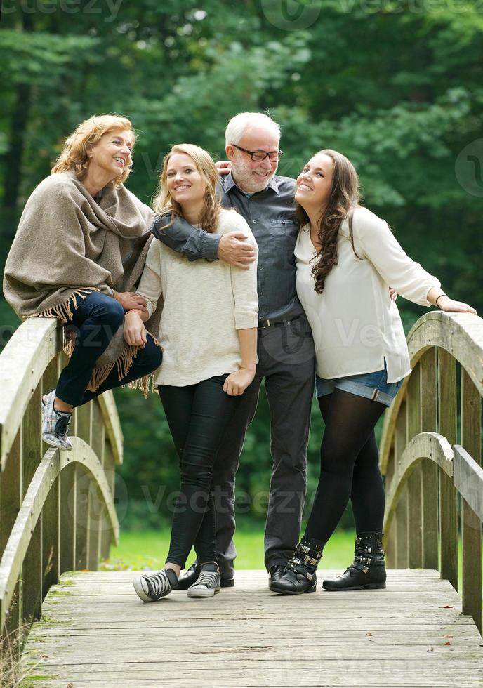 Happy family standing together on a bridge in the woods photo
