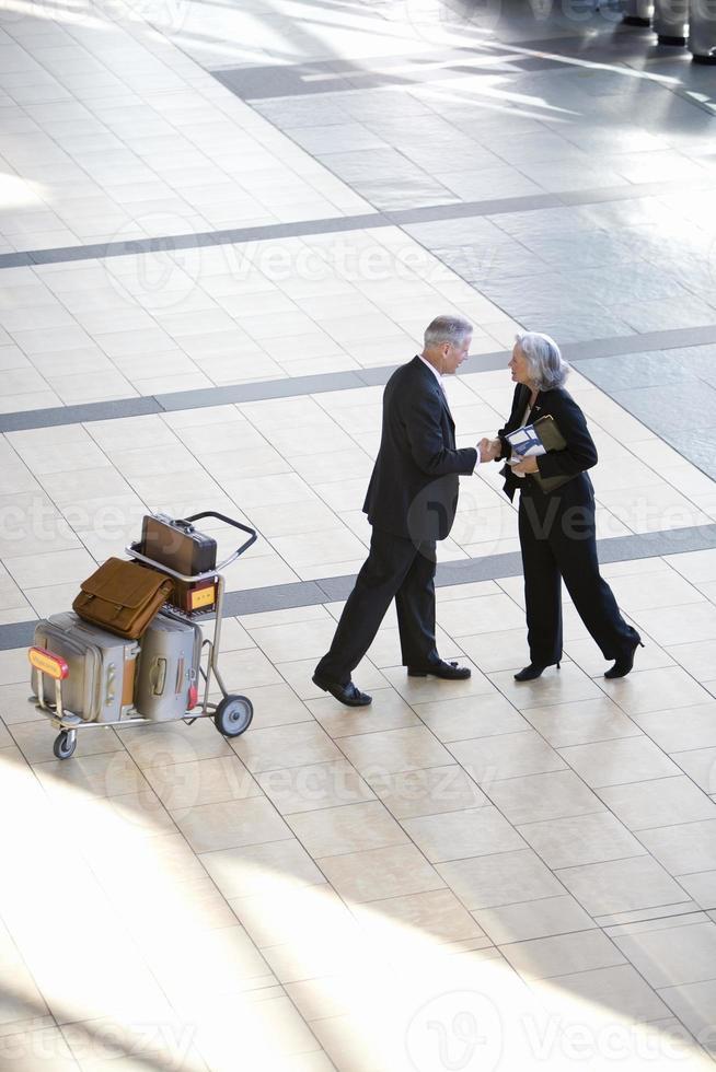 Empresario y mujer estrechándole la mano cerca de la carretilla de equipaje en airp foto