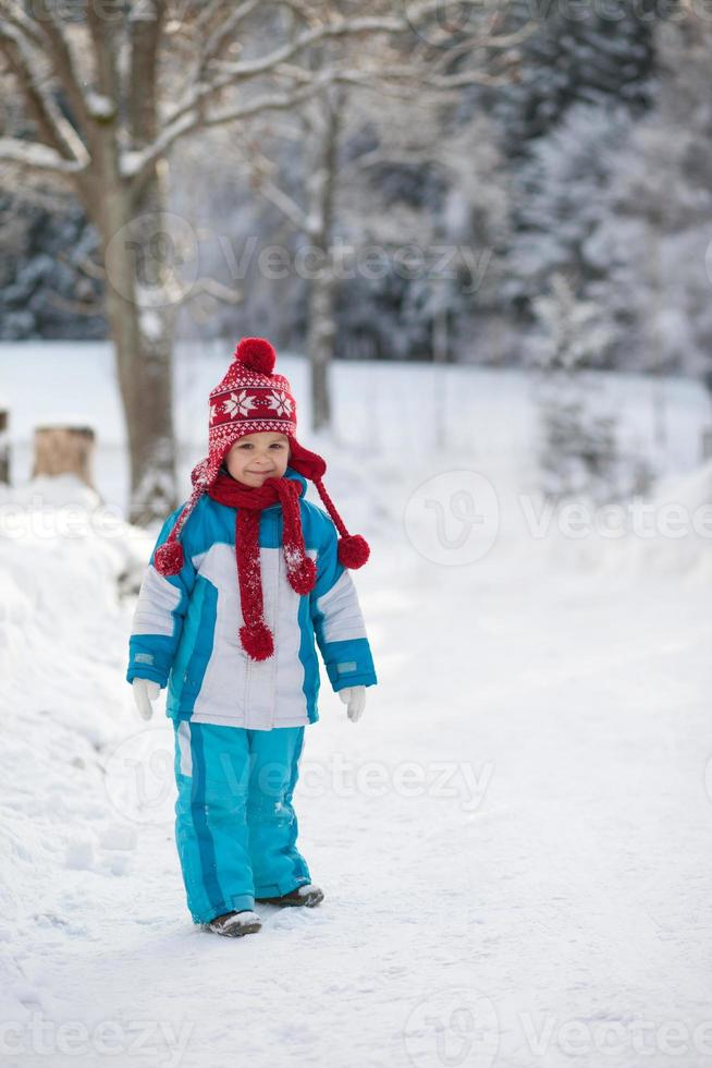 Winter portrait of a boy in the snow photo