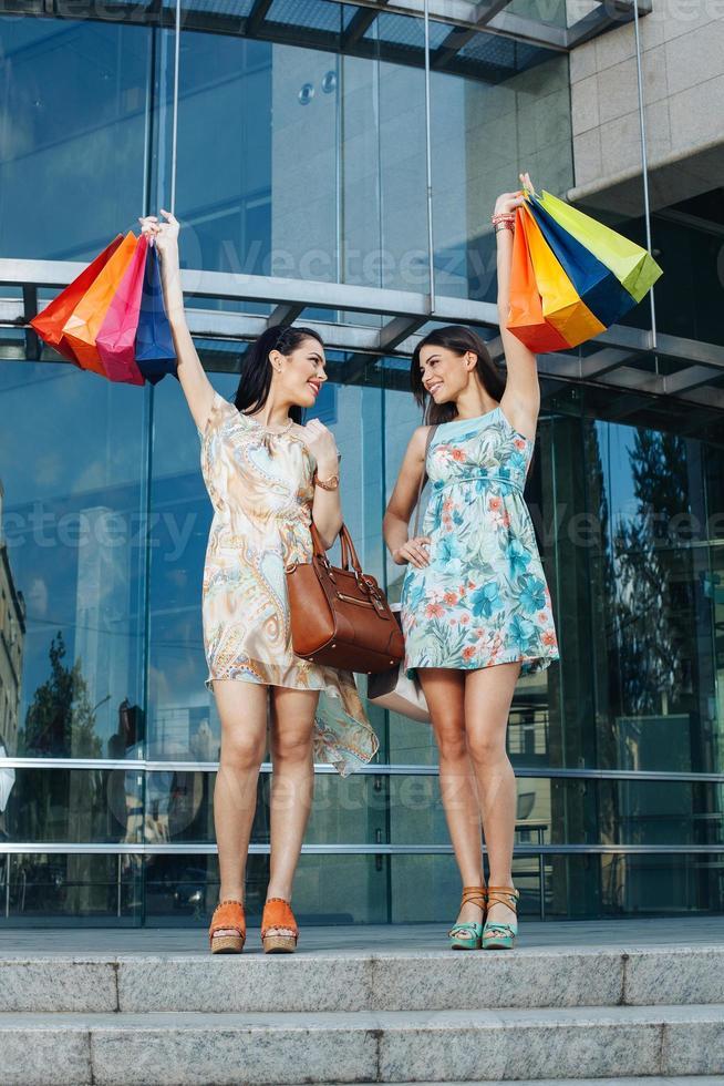 Two attractive women posing with shopping bags photo