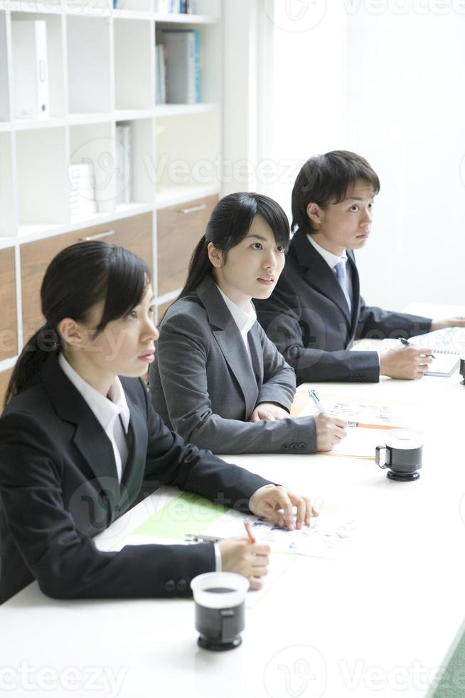 männliche und weibliche neue Mitarbeiter, die eine Ausbildung am Arbeitsplatz erhalten foto