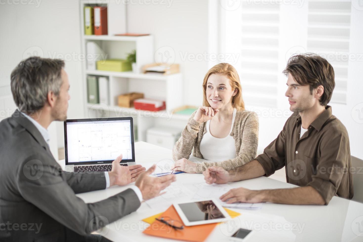 agente de bienes raíces recibe una joven pareja interesada en invertir i foto