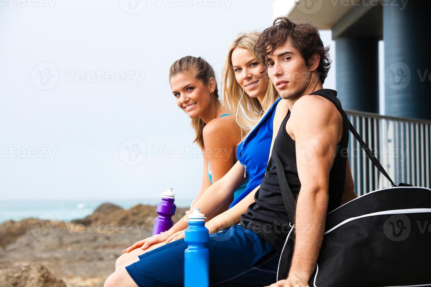 Tres jóvenes sonrientes con botellas de agua en la playa. foto