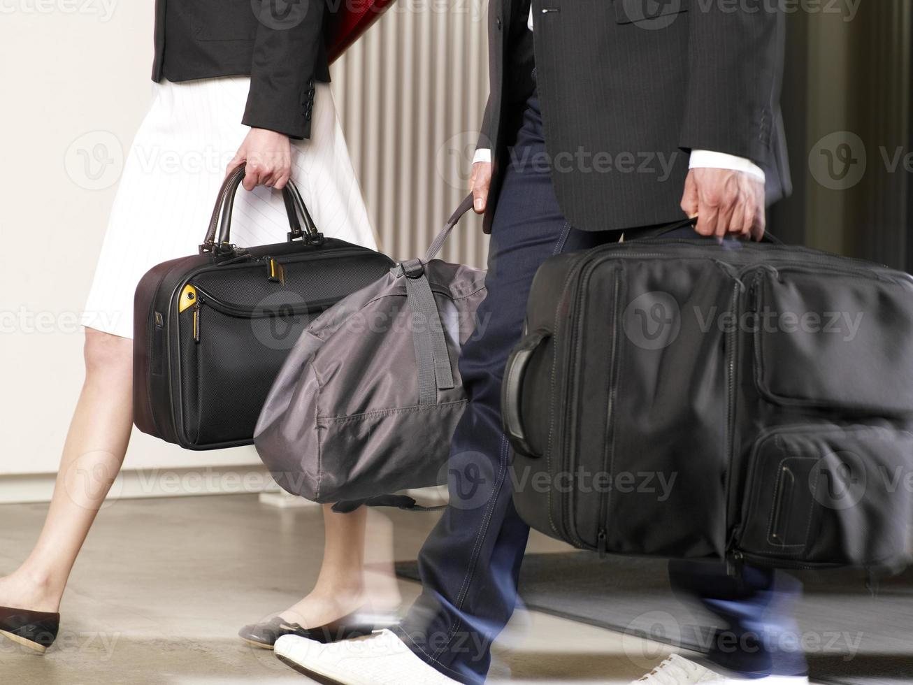 Couple carrying their luggage in a hotel. photo