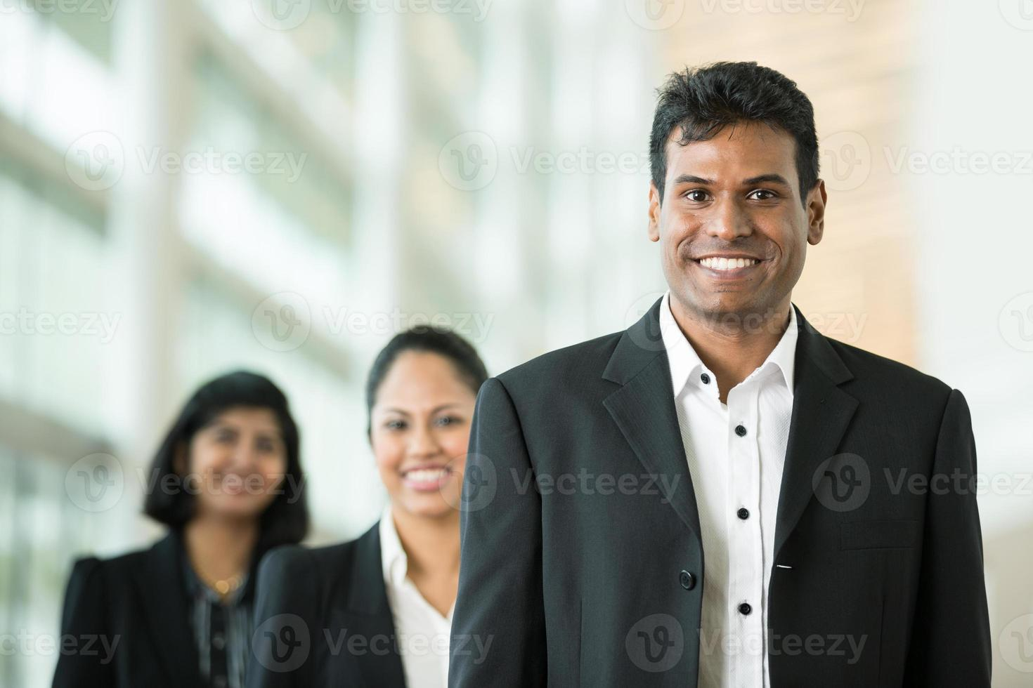 Three business people wearing black suits indoors photo