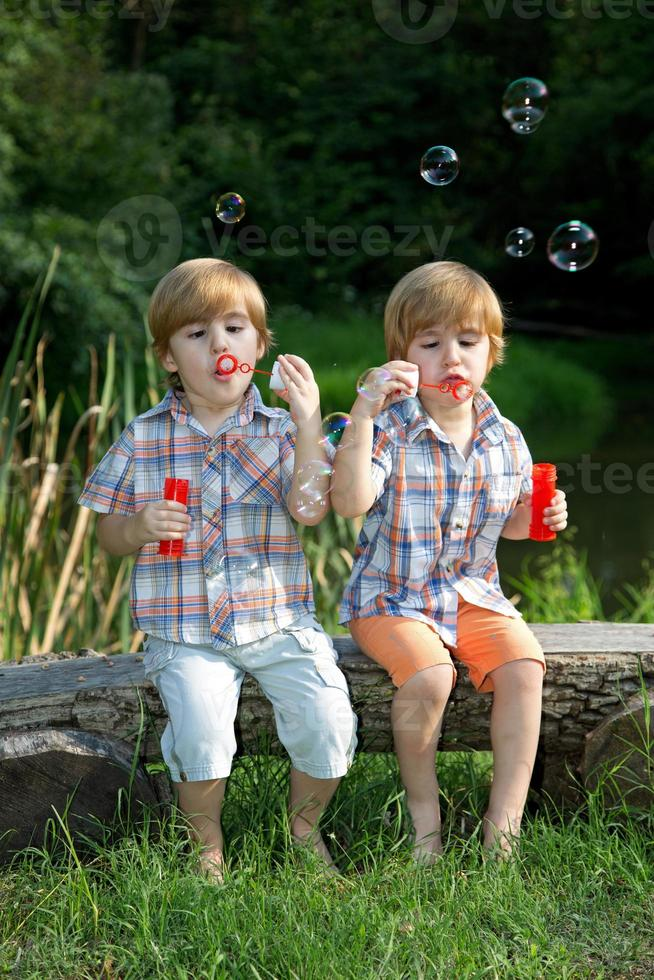 Hermanitos gemelos soplando pompas de jabón en el parque de verano foto