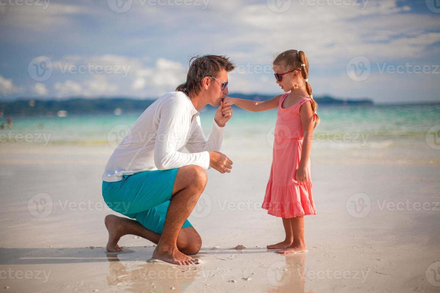 Papá besando la mano de su pequeña hija en la playa exótica foto