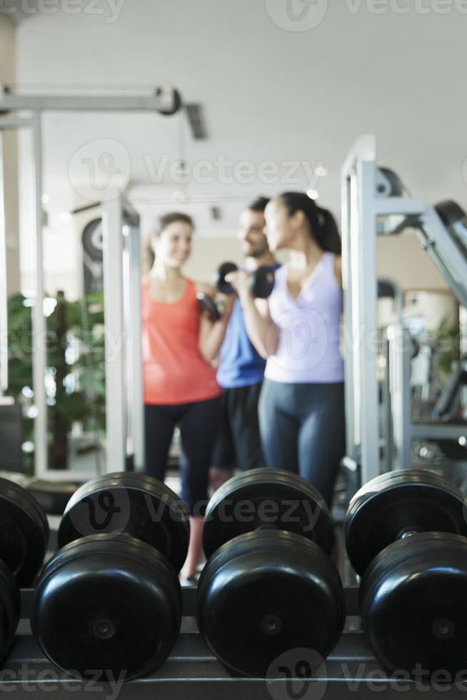 Three people weightlifting, focus on the weights photo