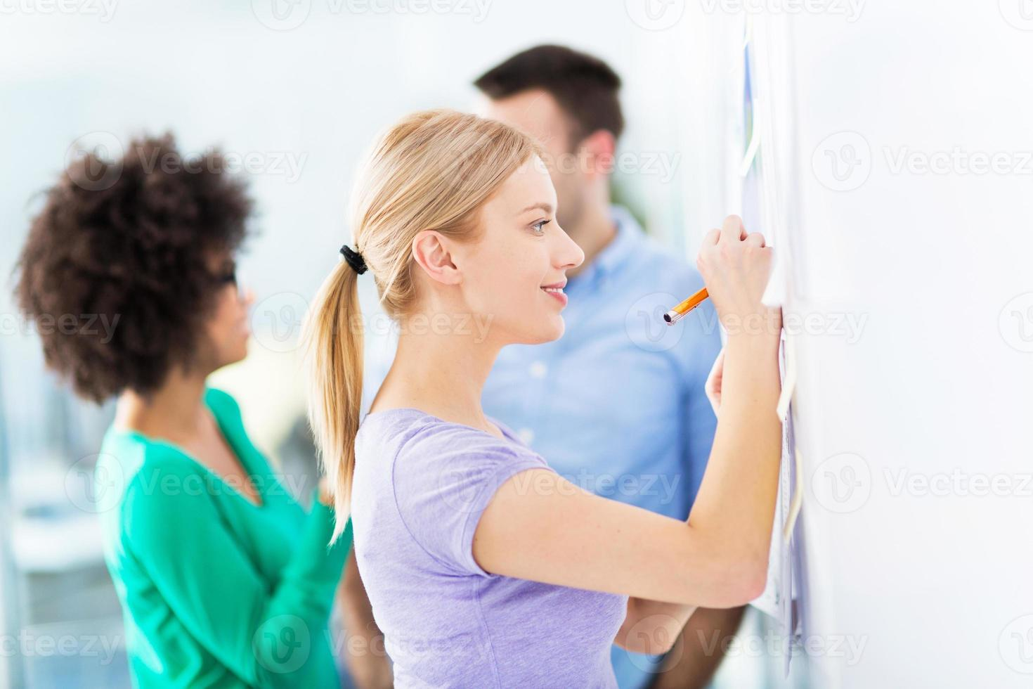 Woman writing ideas on adhesive notes photo