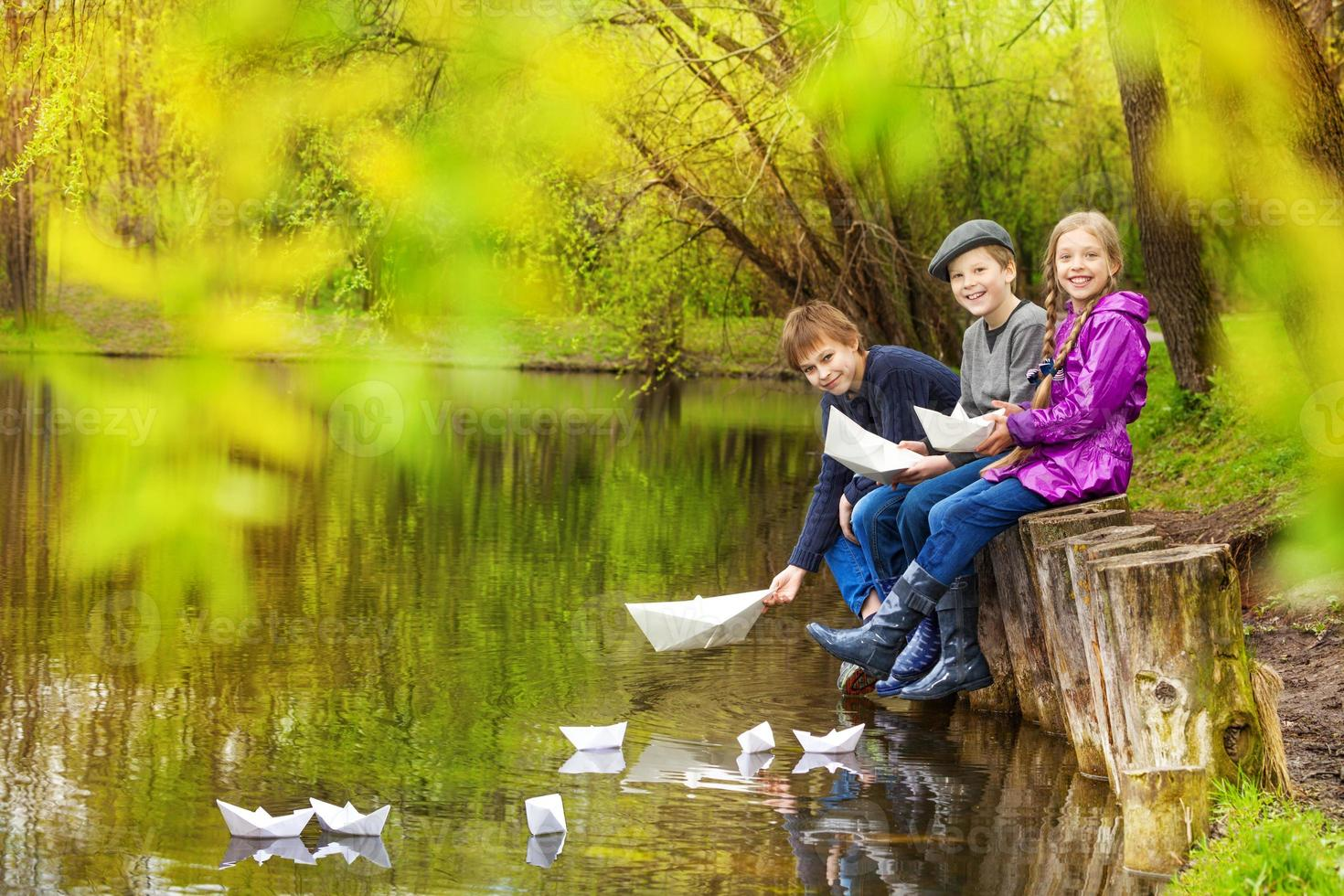 Smiling friends sit putting paper boats on pond photo