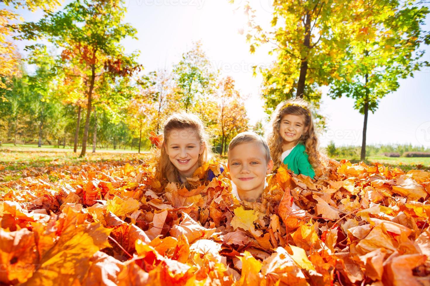 Niños divirtiéndose tirado en el suelo con hojas foto