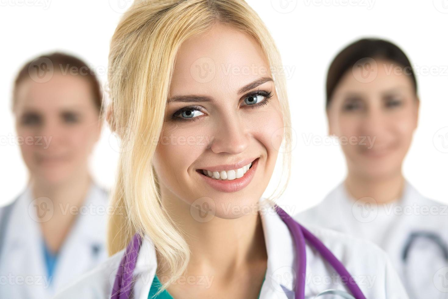 Portrait of young blonde female doctor surrounded by medical tea photo