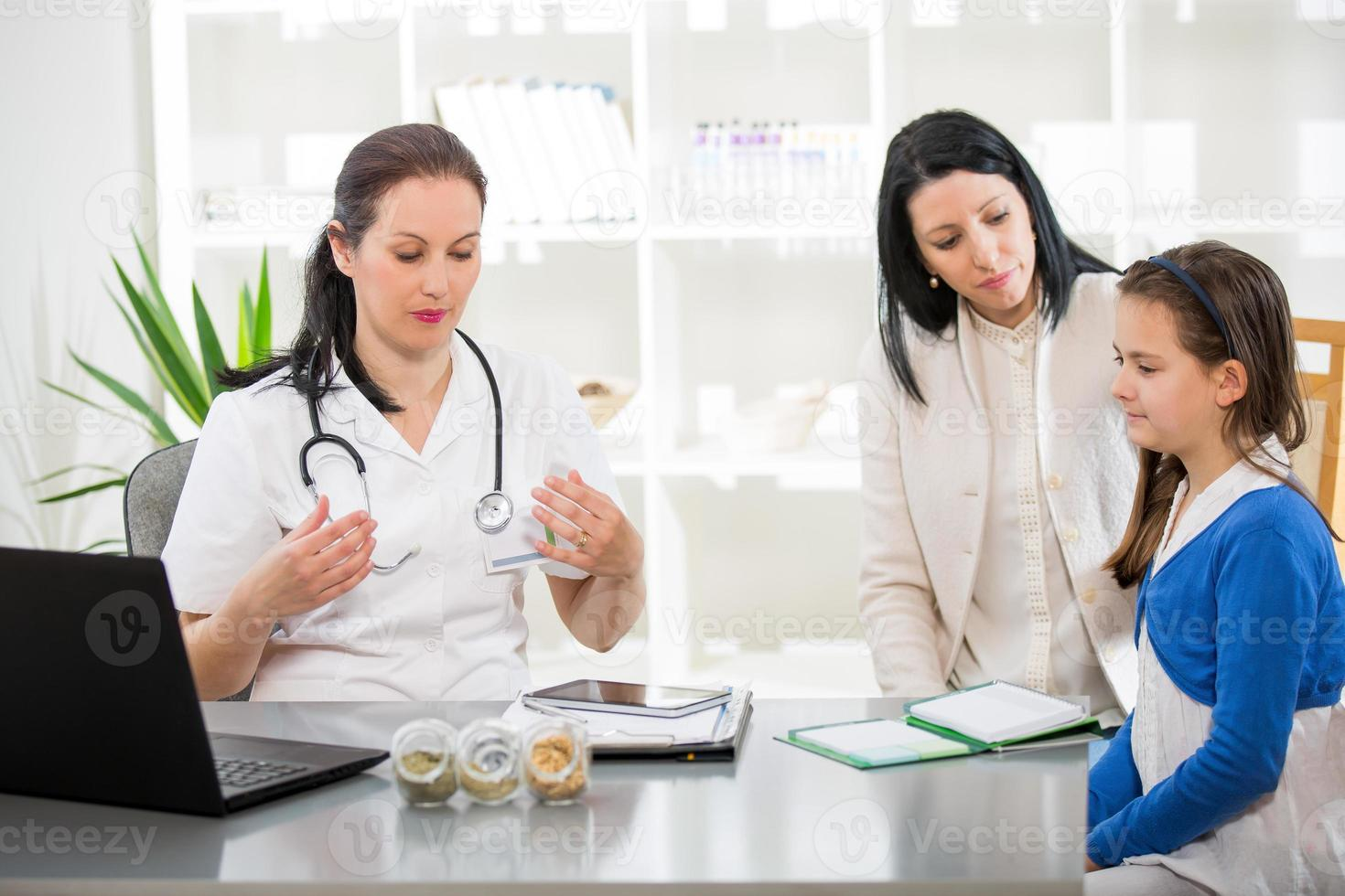 Young woman and her daughter at the doctor homeopaths. photo