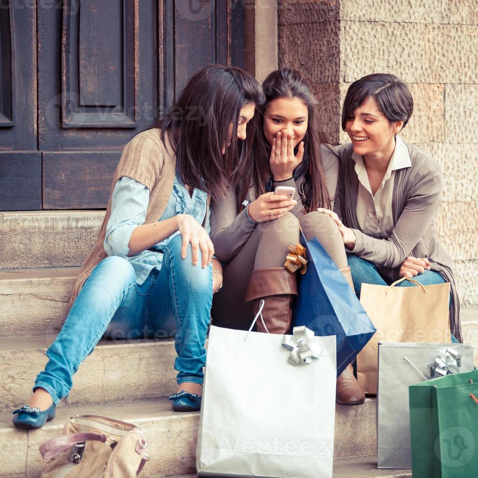 mooie jonge vrouwen chatten met behulp van mobiele telefoon foto