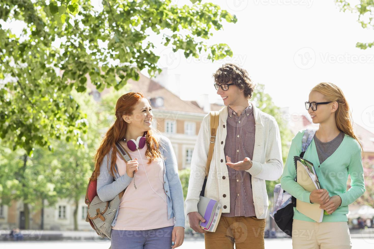 Young college students talking while walking on street photo