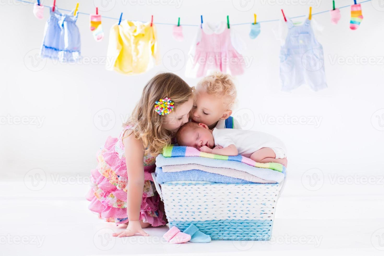Brother and sister kissing newborn baby photo