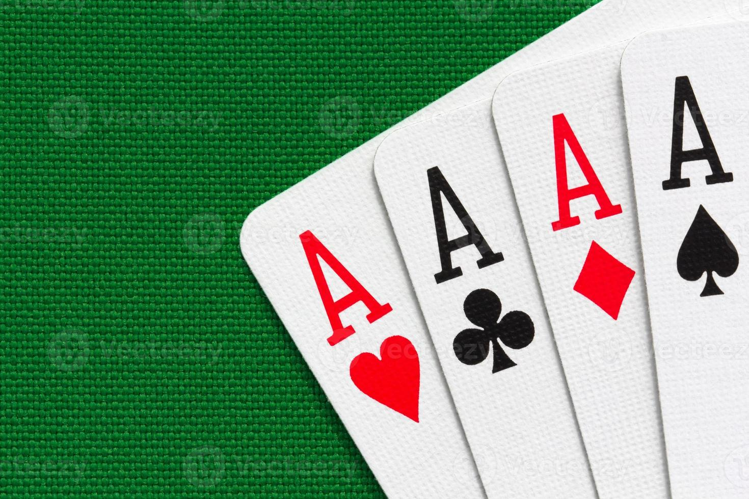 Four aces over green textile background photo