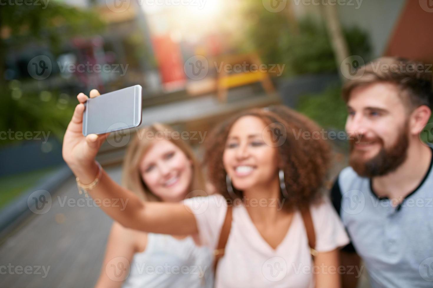 mujer joven tomando selfie con amigo foto