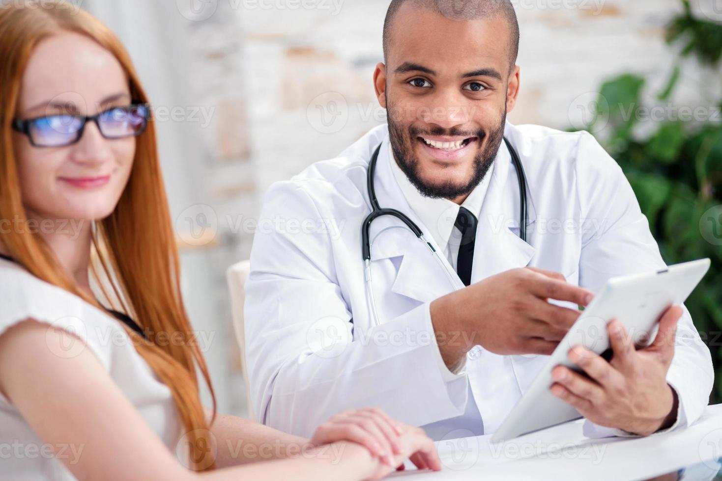 médico alegre, segurando um tablet nas mãos e olhando foto