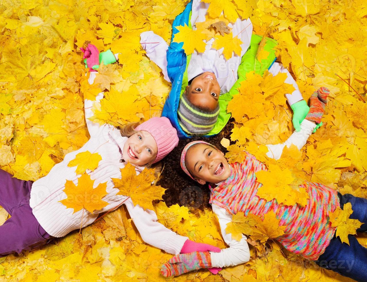 Kids play with autumn maple orange leaves photo