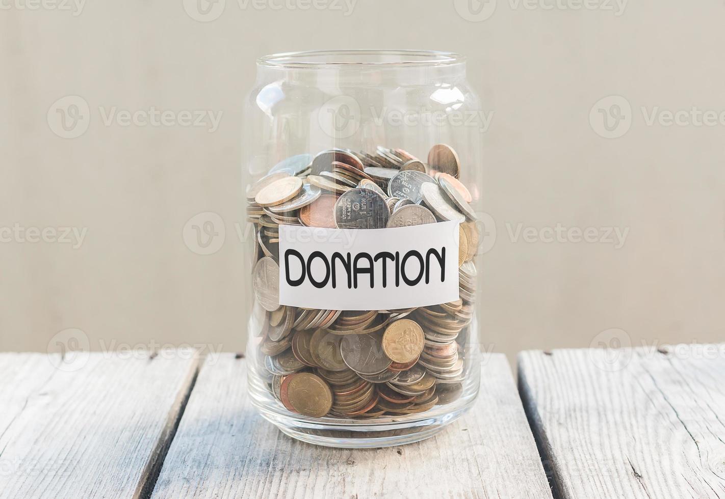 tarro de dinero con monedas en la mesa de madera foto