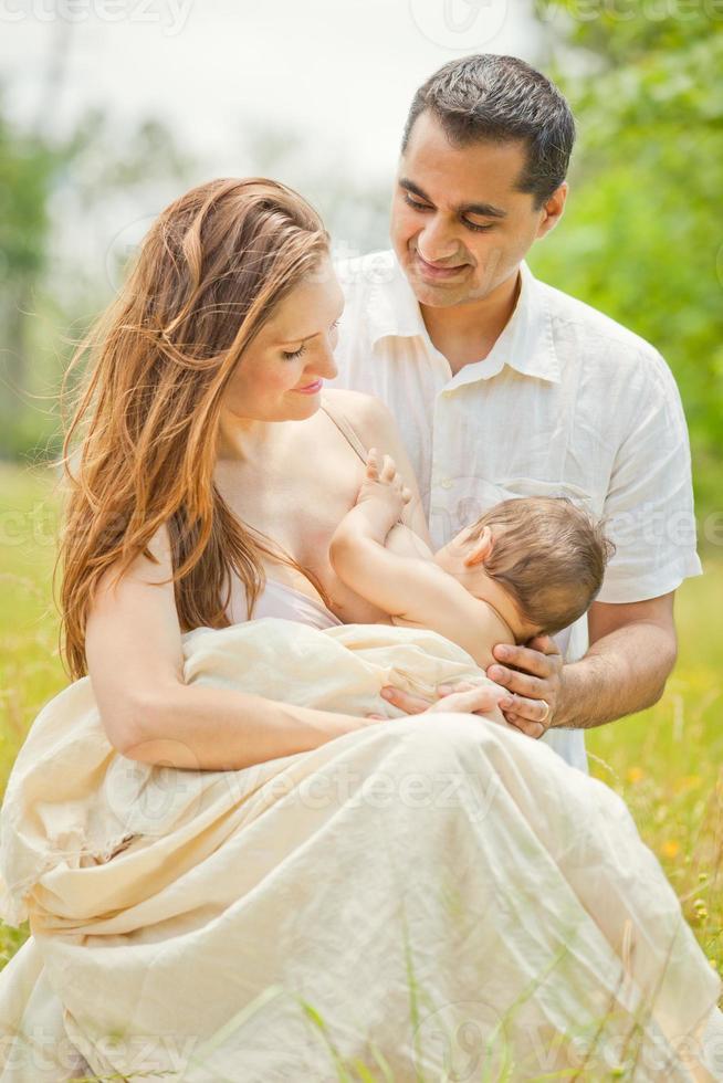madre amamantando bebé con esposo en romántico al aire libre foto