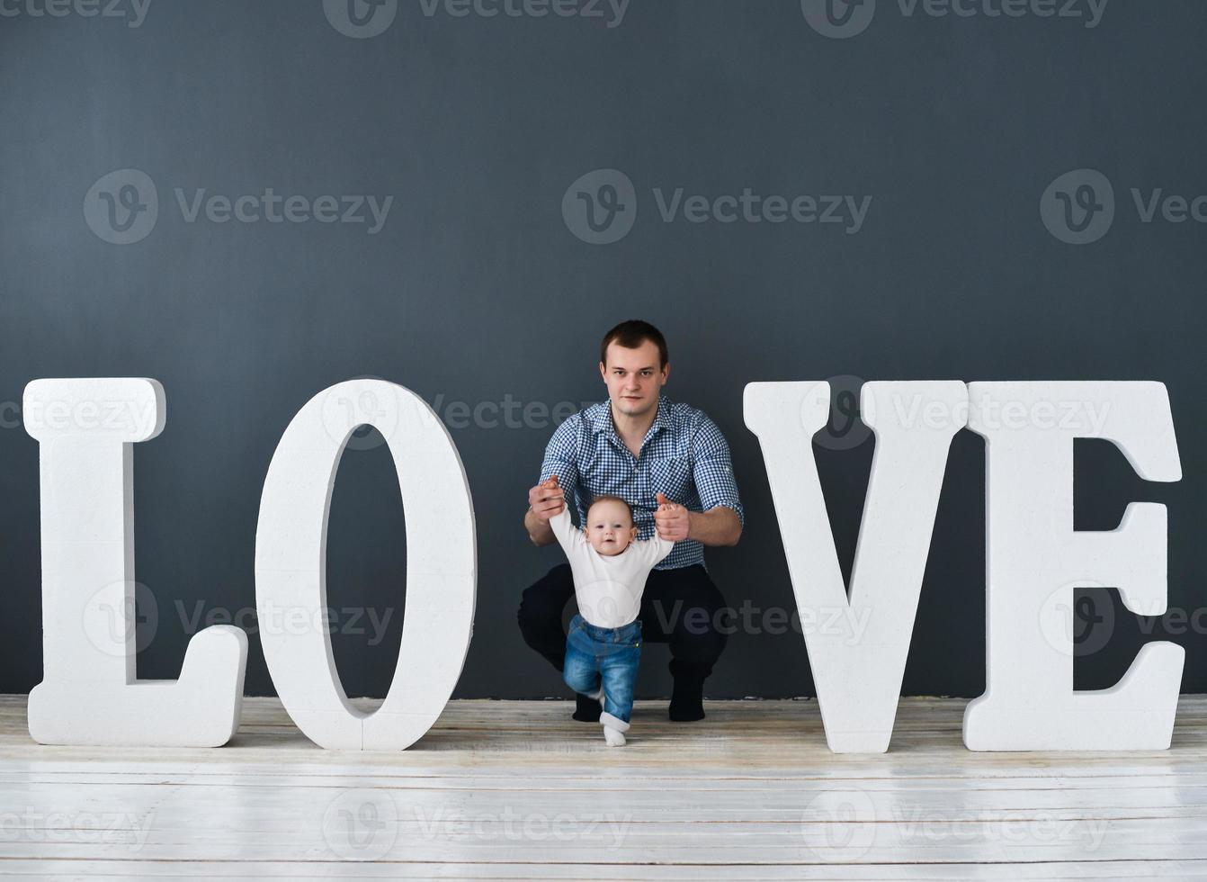 Happy father carrying son isolated on gray background photo