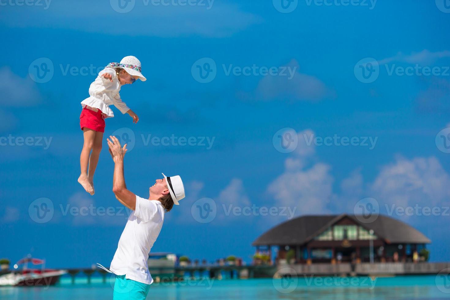 Adorable niña y feliz padre durante vacaciones en la playa tropical foto
