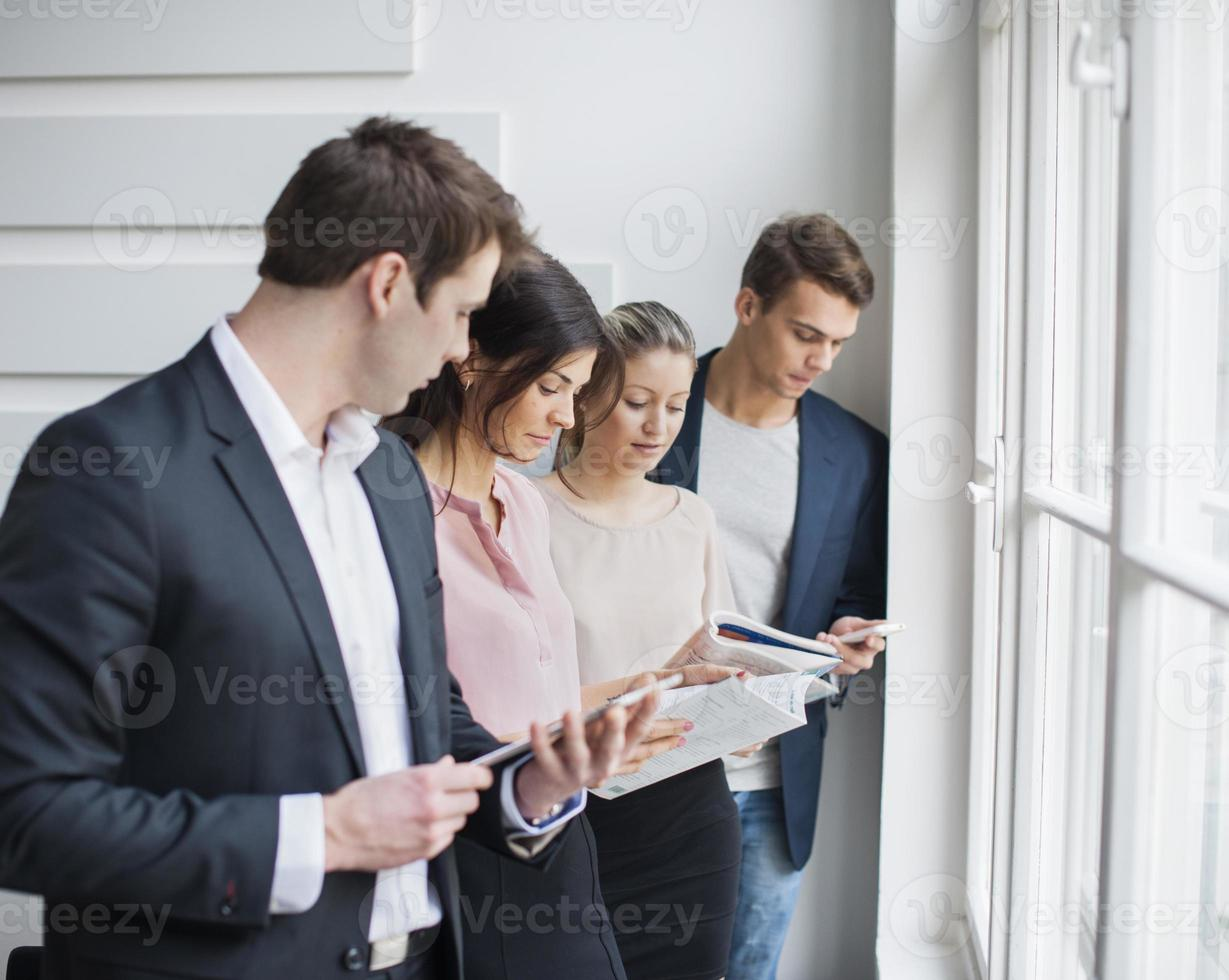 Young business people working by window in office photo