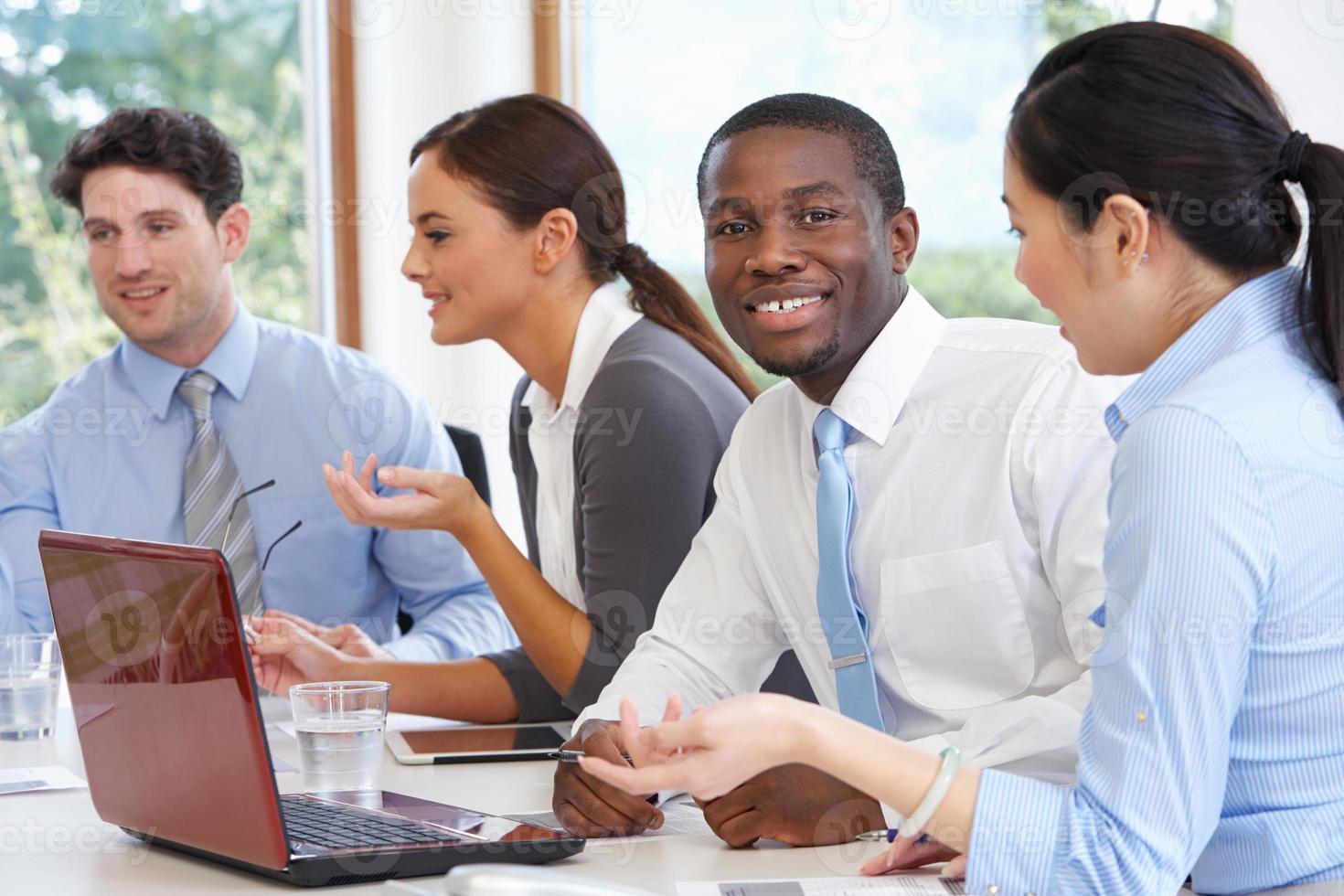 Grupo de empresarios reunidos alrededor de la mesa de la sala de juntas foto